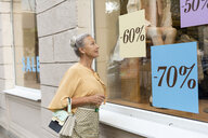 Smiling senior woman looking in shop window of a boutique - VGF00037