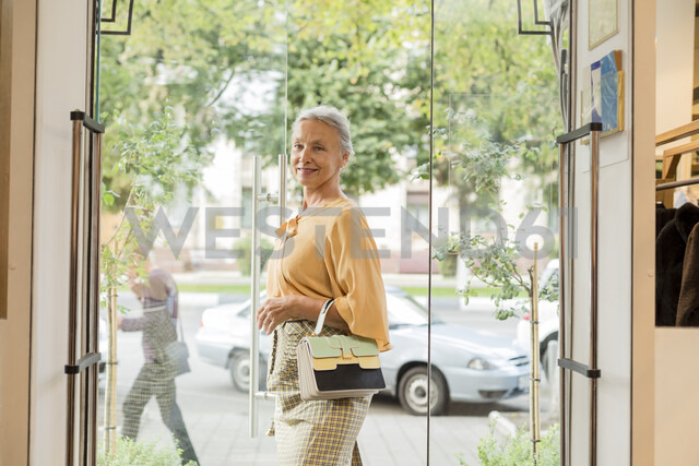 Smiling senior woman walking along a boutique - VGF00040