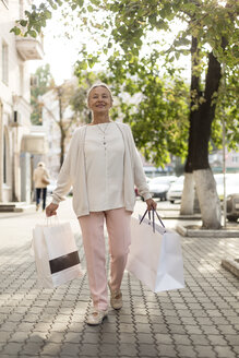 Smiling senior woman walking on pavement with shopping bags - VGF00043