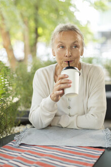 Senior woman with a drink at an outdoor cafe - VGF00046