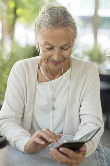 Smiling senior woman at an outdoor cafe with cell phone and earphones - VGF00052