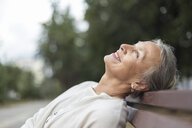 Smiling senior woman relaxing on a bench looking up - VGF00061