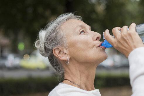 Senior woman outdoors drinking water from bottle - VGF00067