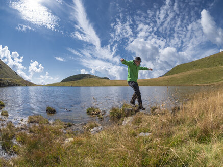Italy, Lombardy, hiker jumping at lakeside - LAF02103