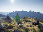 Italy, Lombardy, Bergamasque Prealps, hiker sitting on viewpoint of Monte Gardena, Cima Bagozza against the sun - LAF02112