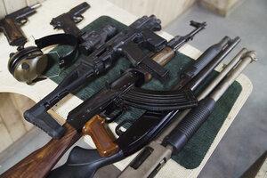 Assortment of guns on table in an indoor shooting range - KKAF02579