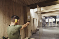 Man aiming with a pistol in an indoor shooting range - KKAF02582