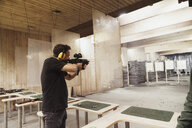 Man aiming with a rifle in an indoor shooting range - KKAF02585