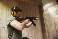 Man aiming with a rifle in an indoor shooting range - KKAF02588
