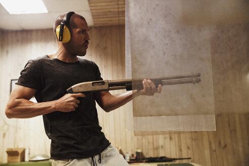 Man shooting with a rifle in an indoor shooting range - KKAF02591
