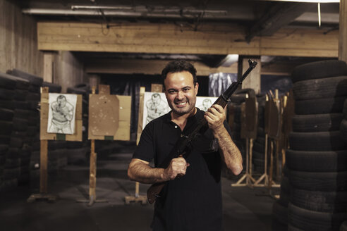 Portrait of aggressive man holding a rifle in an indoor shooting range - KKAF02594