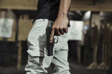 Close-up of man holding a pistol in an indoor shooting range - KKAF02600