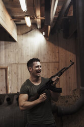 Laughing man holding a rifle in an indoor shooting range - KKAF02603