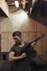 Man holding a rifle in an indoor shooting range - KKAF02606