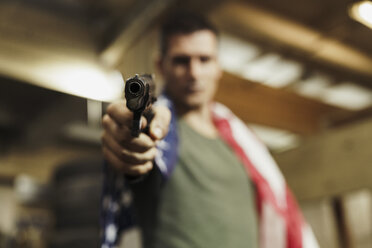 Close-up of man wearing American flag aiming with a gun - KKAF02612
