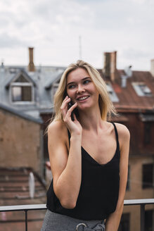 Portrait of smiling blond woman on the phone standing on balcony - KKAF02618