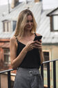 Portrait of smiling blond woman standing on balcony looking at cell phone - KKAF02621
