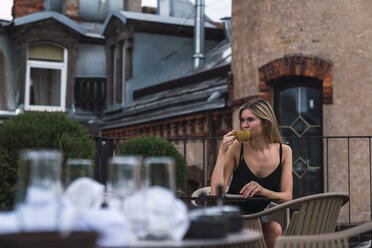 Young woman sitting on roof terrace drinking cup of coffee - KKAF02630