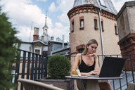 Young woman sitting on roof terrace using laptop - KKAF02636