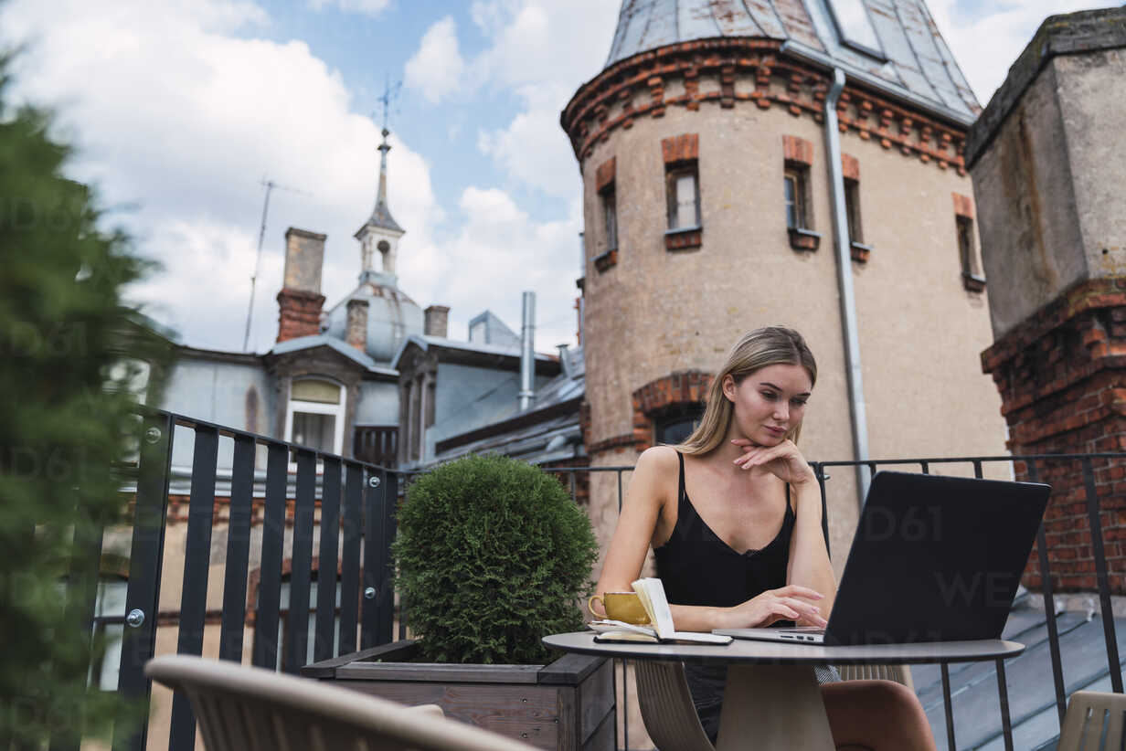 Young woman sitting on roof terrace using laptop - KKAF02636 - Kike Arnaiz/Westend61