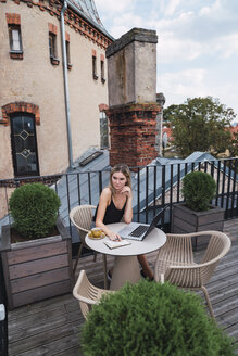 Young woman with laptop and notebook sitting on roof terrace watching something - KKAF02642
