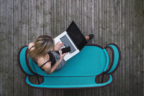 Young woman sitting on turquoise couch on terrace using laptop and cell phone, top view - KKAF02651