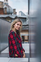 Portrait of smiling blond young woman wearing plaid shirt - KKAF02663