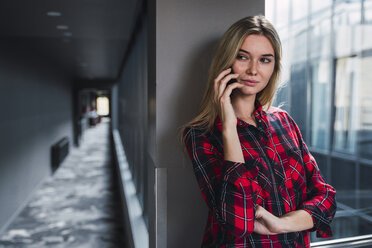 Portrait of young woman on the phone in a modern office building - KKAF02669