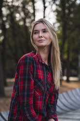 Portrait of blond young woman wearing plaid shirt in autumn - KKAF02672