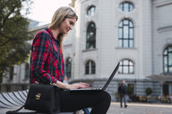 Fashionable young woman sitting on bench outdoors working on laptop - KKAF02675