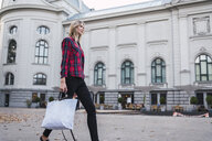 Fashionable young woman with shopping bag walking along - KKAF02681