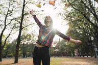 Happy young woman throwing autumn leaves in the air - KKAF02684