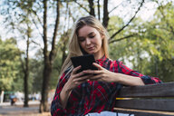 Young woman sitting on bench outdoors using mini tablet - KKAF02687