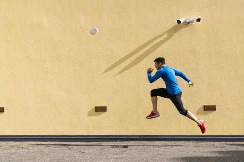 Sportive man exercising at yellow wall with CCTV camera - KKAF02690