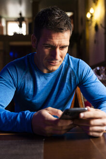 Man wearing sports jersey using cell phone at table - KKAF02693
