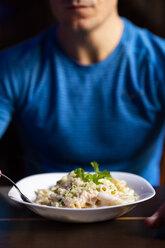 Close-up of athlete eating pasta dish - KKAF02696
