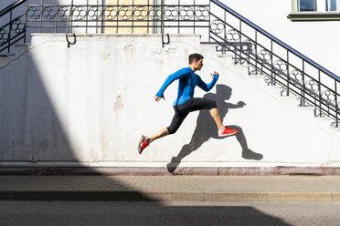 Sportive man exercising on pavement - KKAF02702