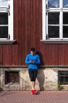 Athlete leaning against house wall using cell phone - KKAF02705
