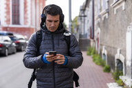 Man in the city on the go with cell phone and headphones - KKAF02711