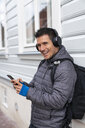 Portrait of laughing man at house wall with cell phone and headphones - KKAF02717