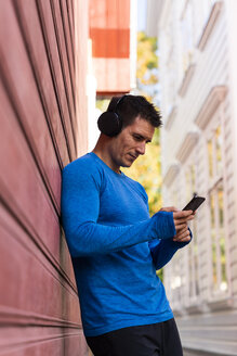Athlete leaning against house wall with cell phone and headphones - KKAF02723