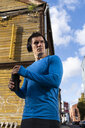 Athlete in the city with headphones and drinking bottle - KKAF02729
