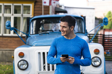 Smiling athlete holding cell phone at pickup truck - KKAF02738