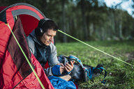 Man camping in Estonia, sitting in his tent, lietsning music from his smartphone - KKA02762
