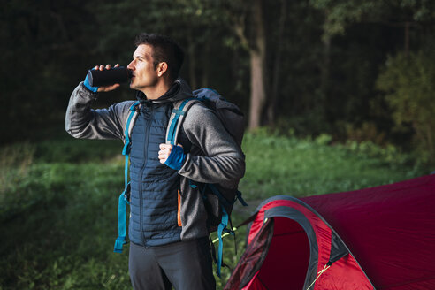 Man camping in Estonia, drinking water - KKA02771