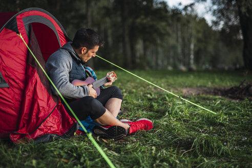 Man camping in Estonia, sitting in his tent, playing the ukulele - KKA02780