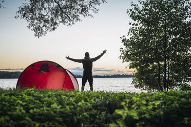 Man camping in Estonia, stretching at lake - KKA02783