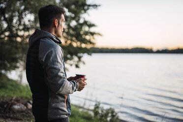 Man looking at the lake, drinking coffee - KKA02786
