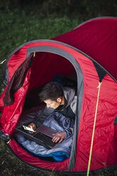Man camping in Estonia, sitting in tent, using laptop - KKA02789