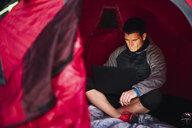 Man camping in Estonia, sitting in tent, using laptop - KKA02792